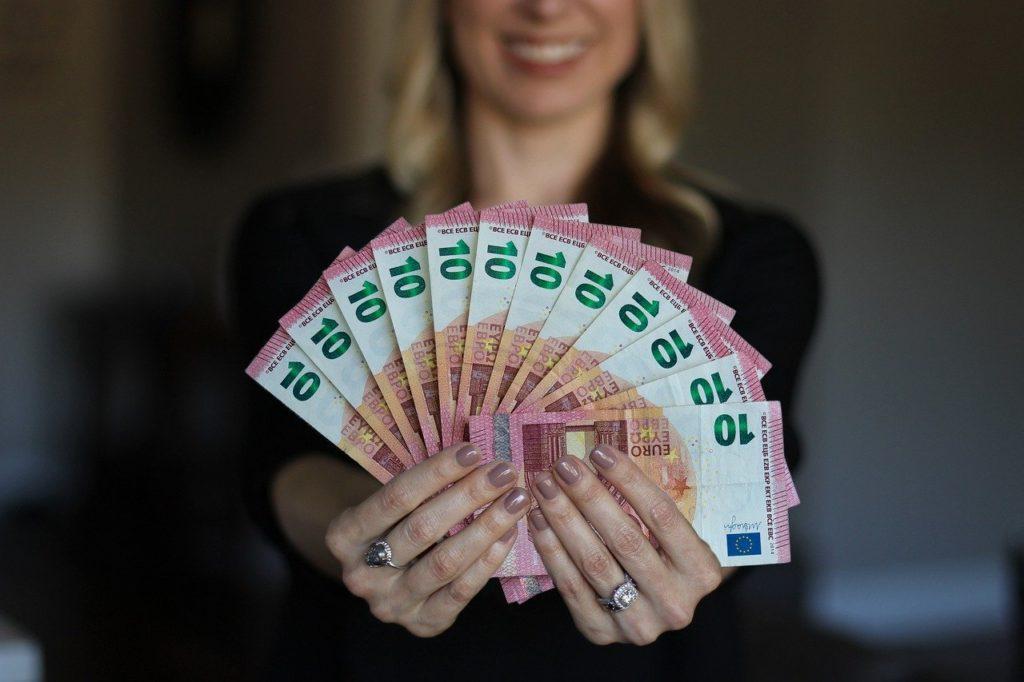 お金を手に微笑む女性