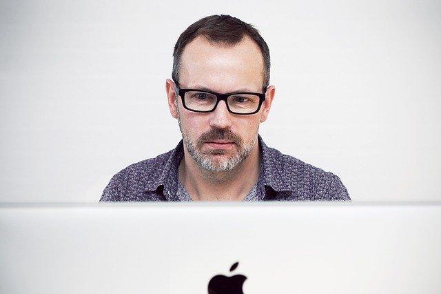 ノートパソコンを見る初老の男性