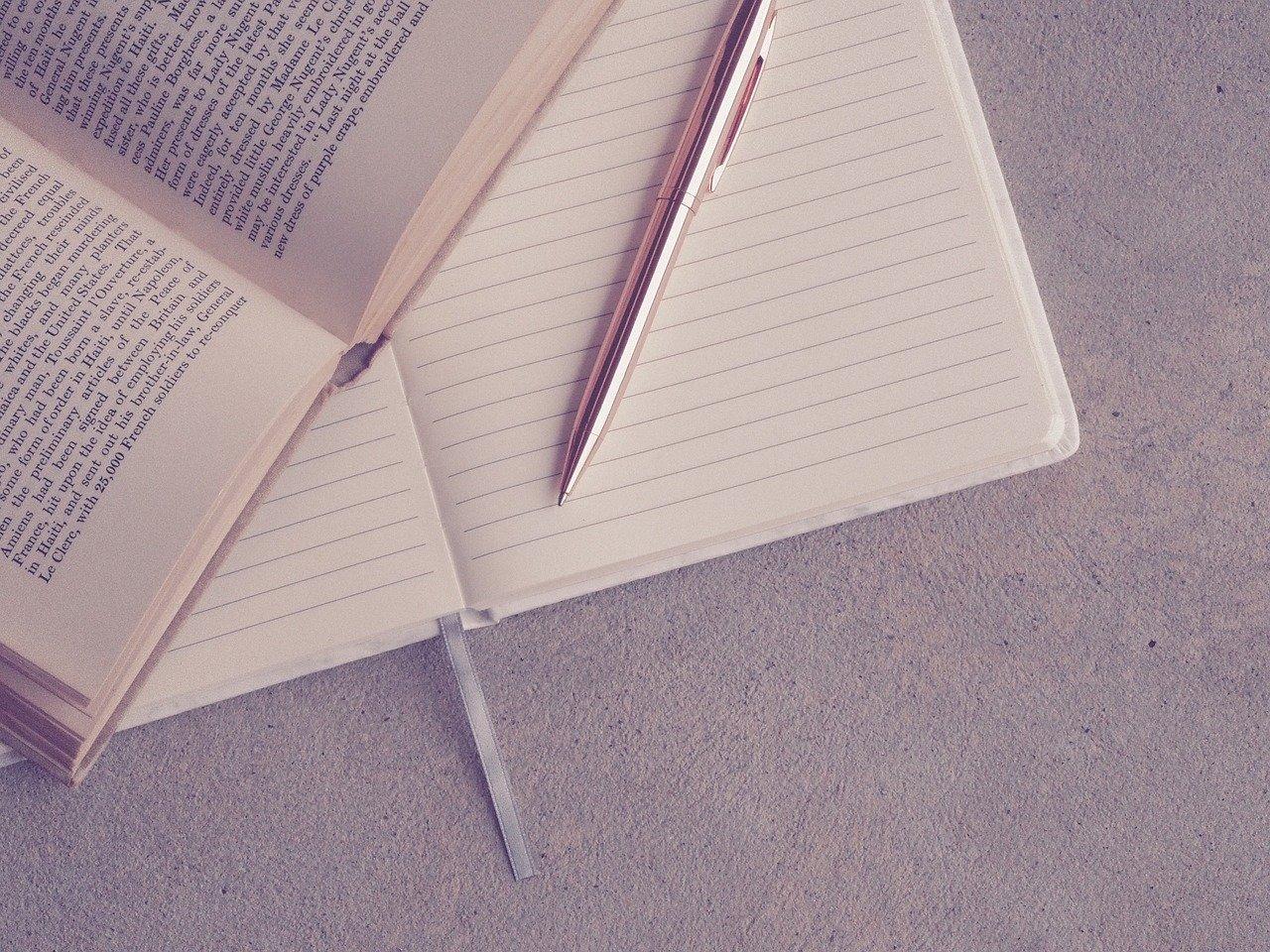 開いたノートや本とペン
