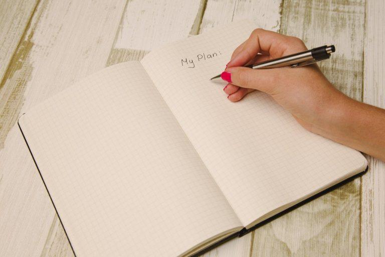 ノートに書き込む人の手