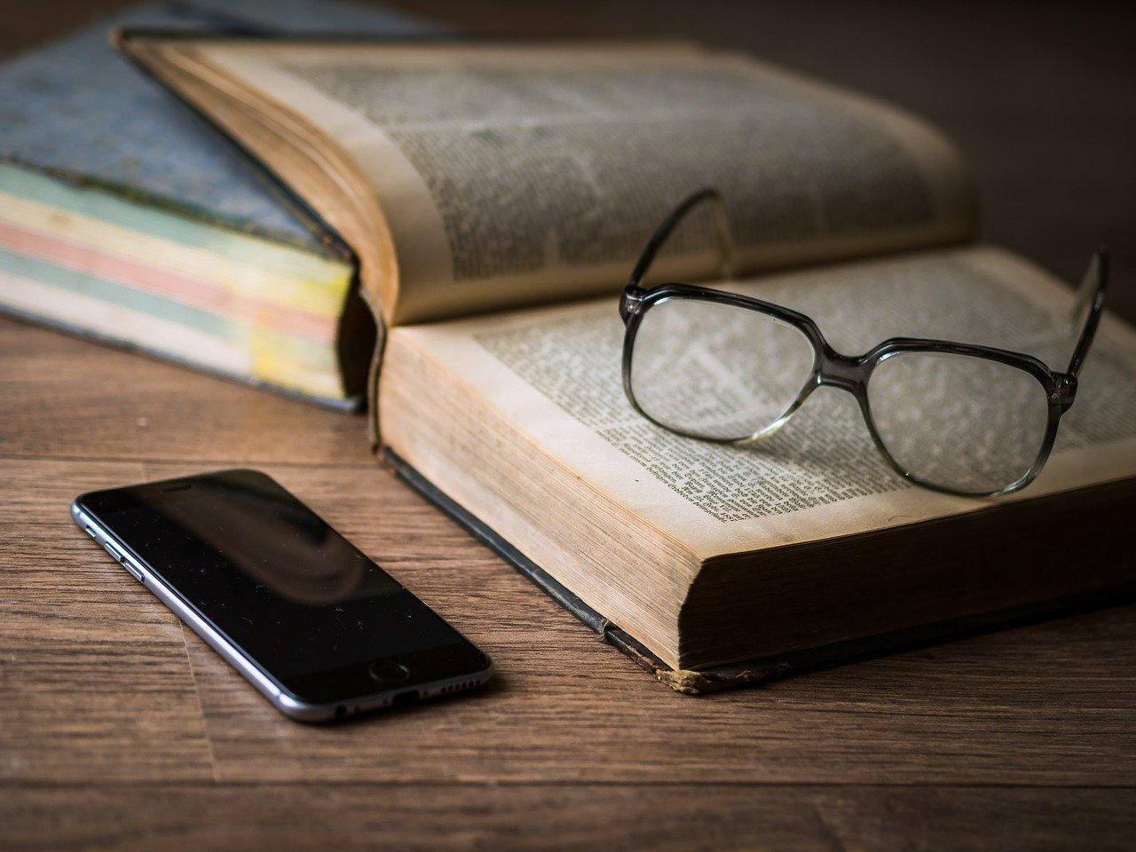 本の上に置かれたメガネとスマホ