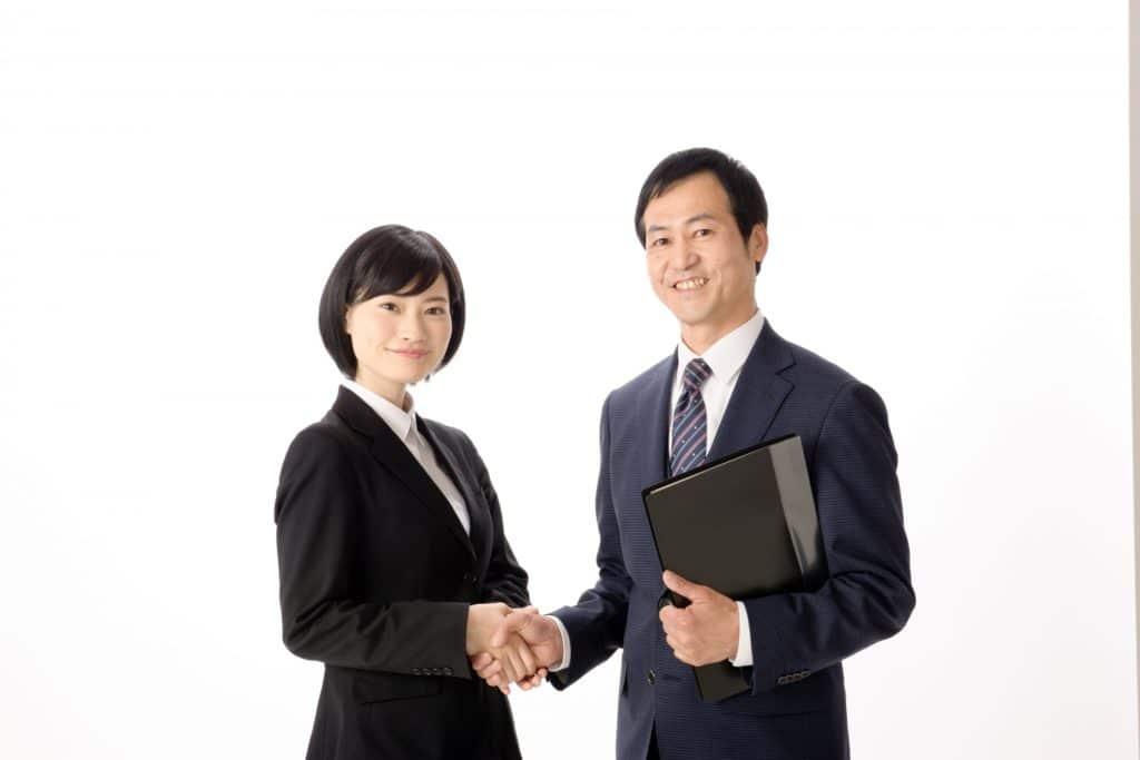 握手するスーツ姿の男女