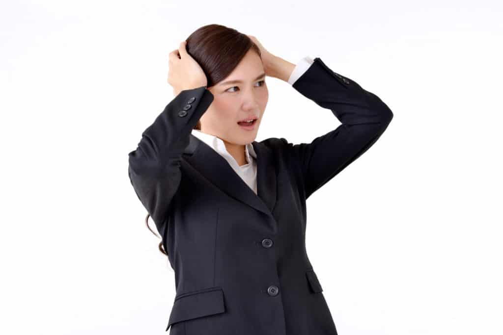 頭を抱えるスーツ姿の女性