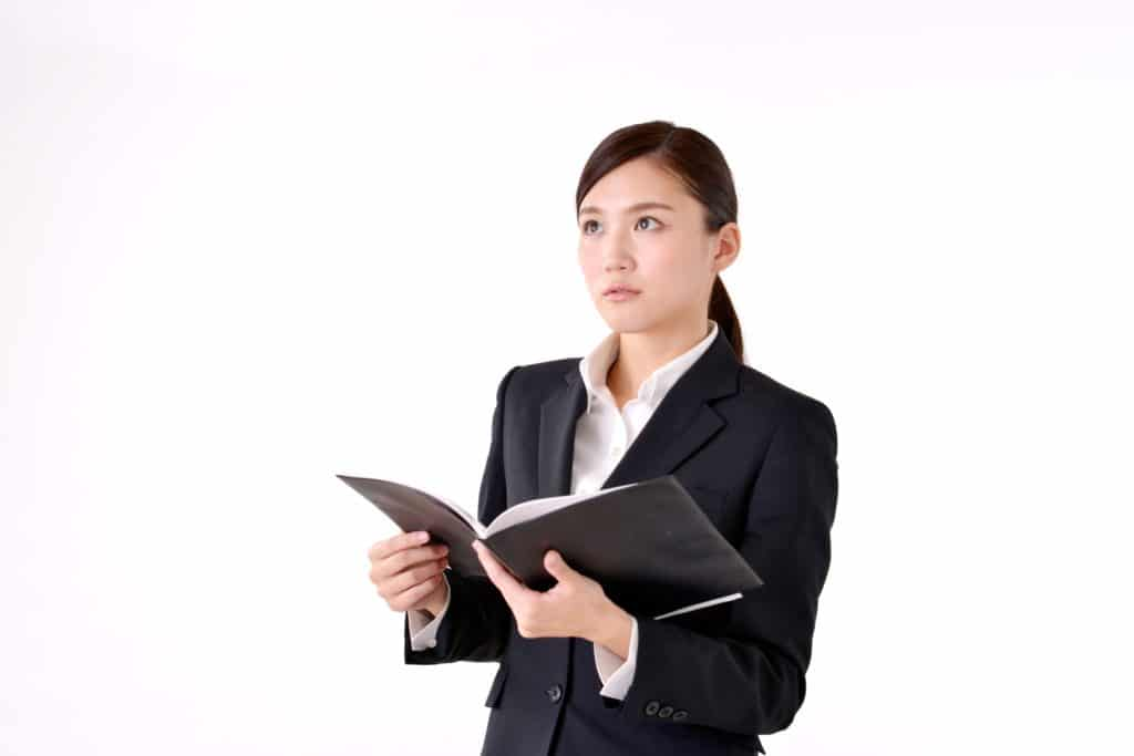 本を開くスーツの女性