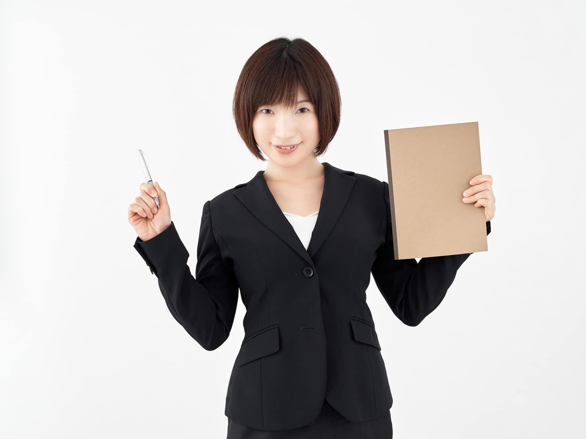 ペンとノートを持つ女性