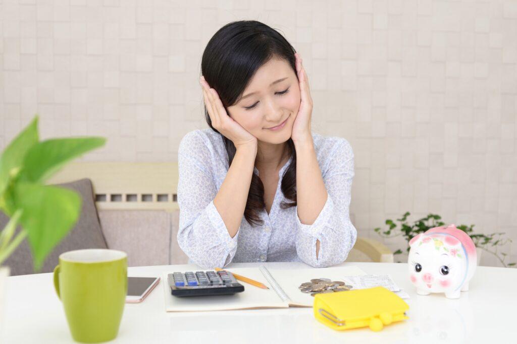 お金の計算で頭を抱える女性