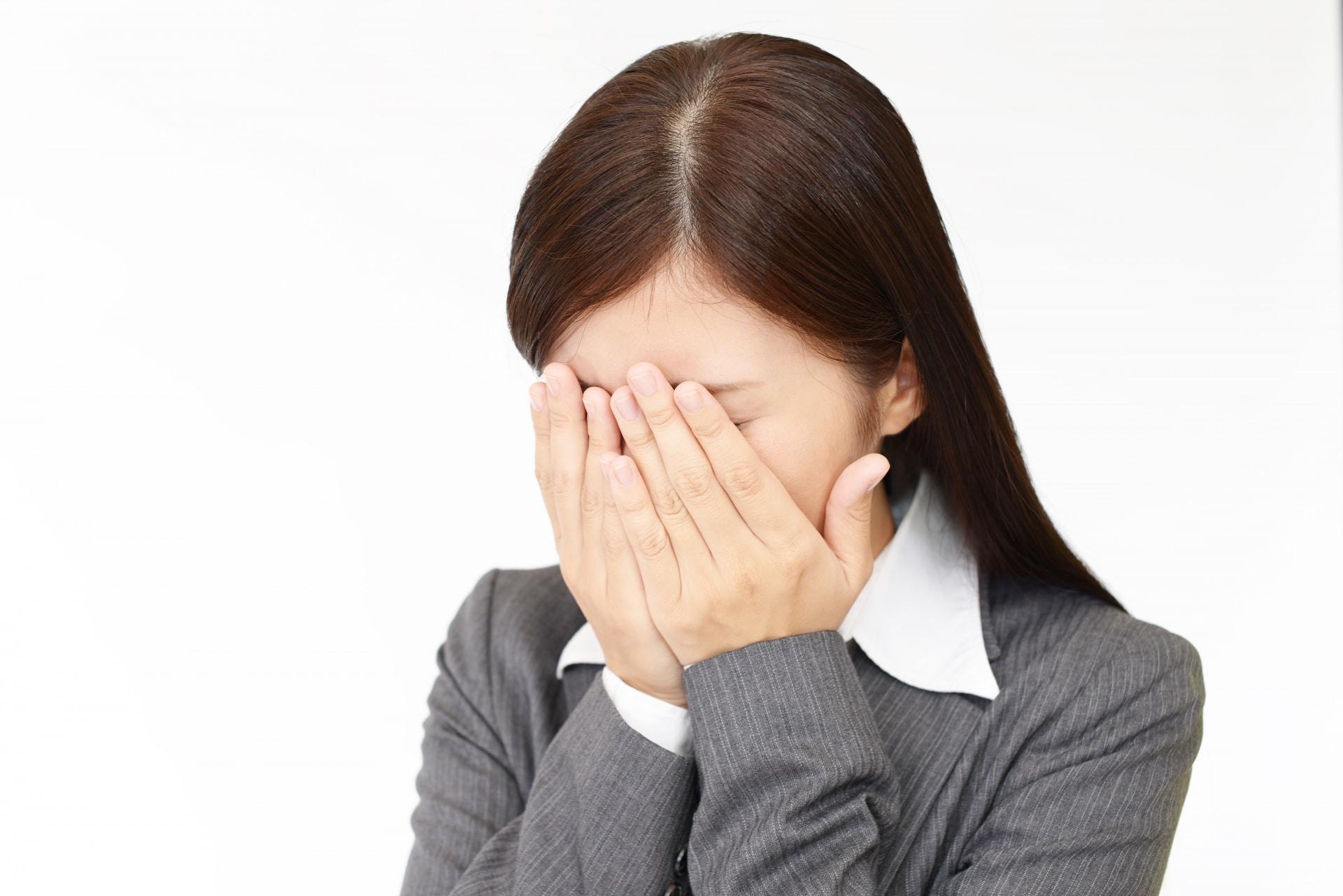顔を覆って泣くスーツ姿の女性