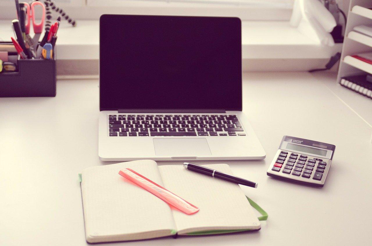 開いたノートと電卓とノートPC