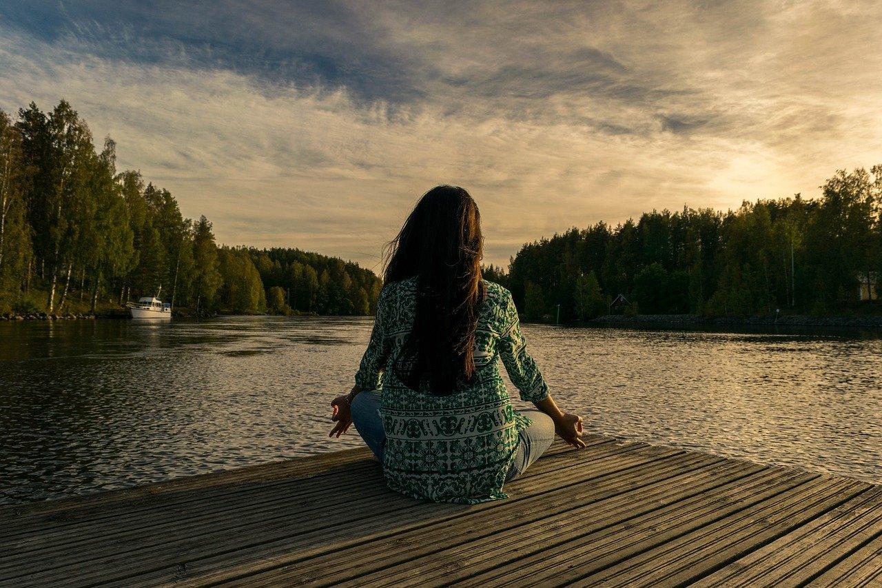 ヨガをする女性、水辺、座る