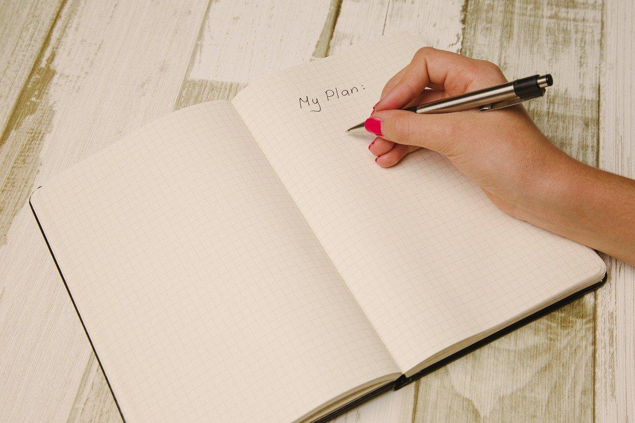 開いたノートとペンを持つ手