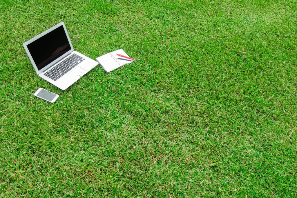 芝生の上のノートPCとスマホ