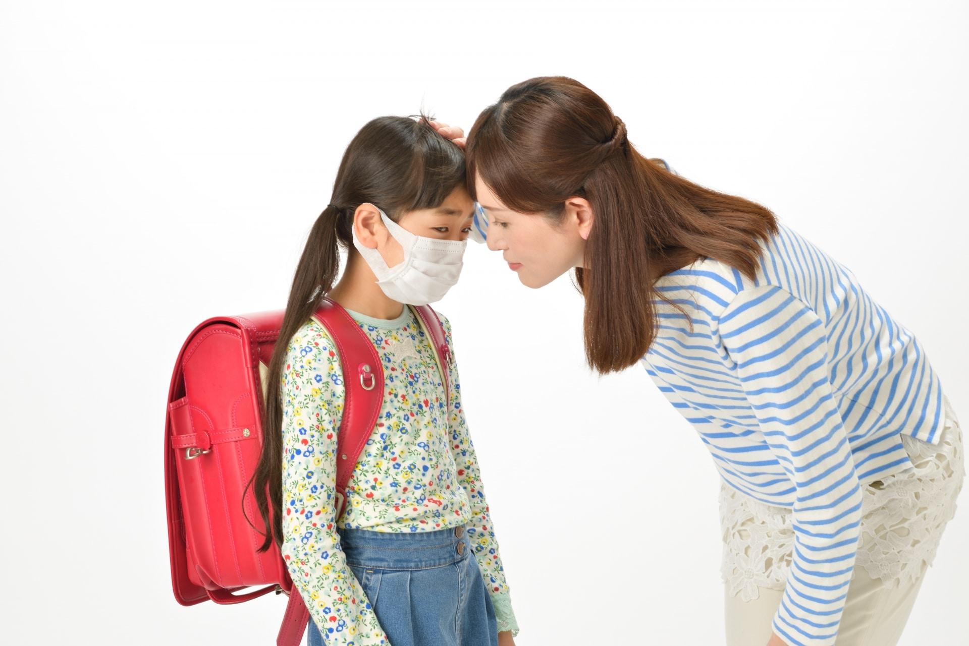 マスクをした子供、熱を測る女性