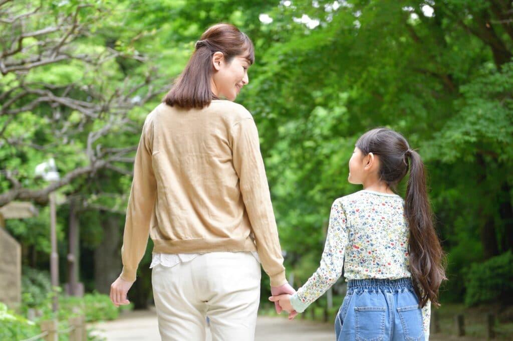 手をつなぐ娘と母親
