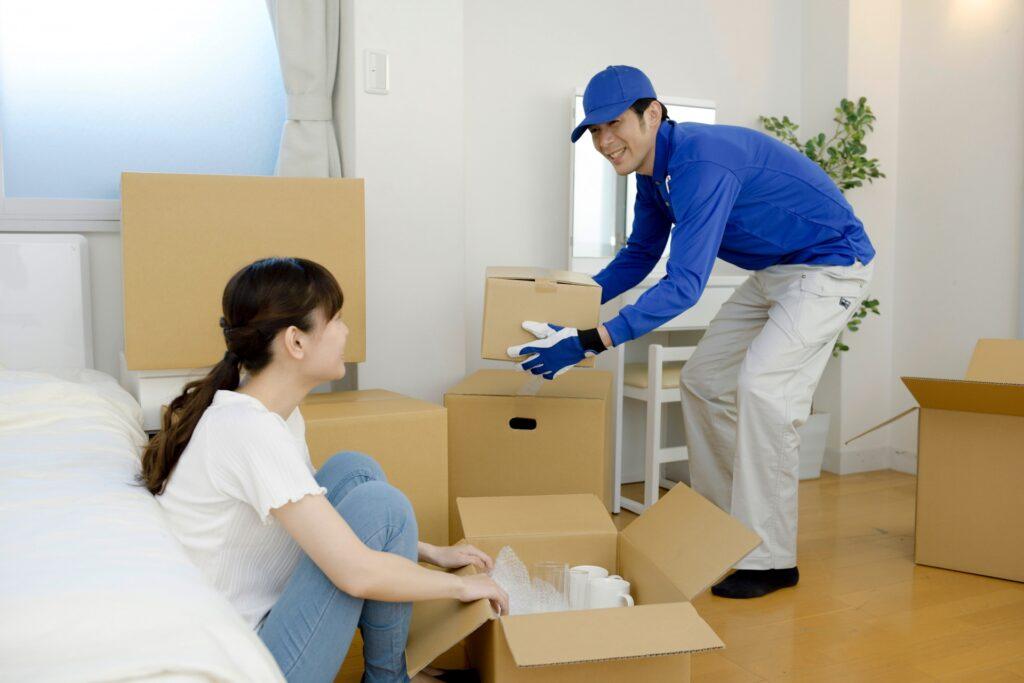 荷造りをする女性、引っ越し業者、段ボール