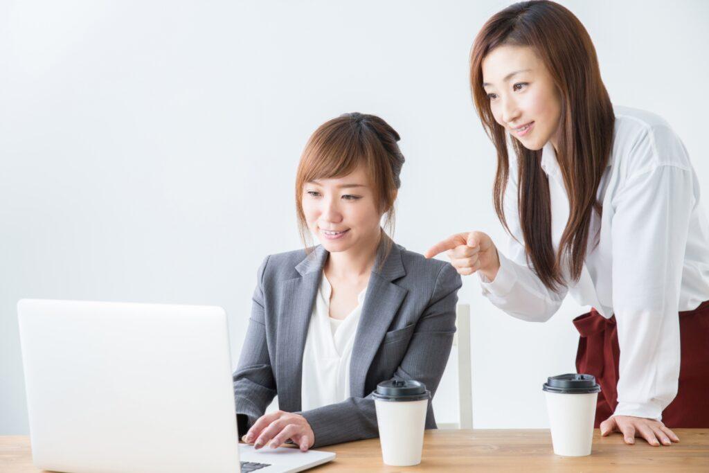 パソコンを使う女性、アドバイスをする女性