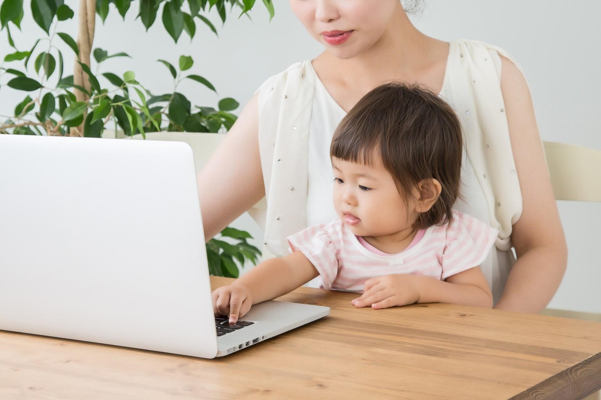 パソコンを触る子どもと母親