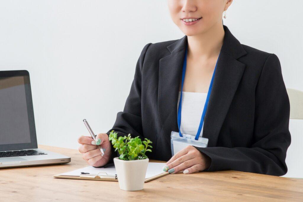 ペンを持って座る笑顔の女性