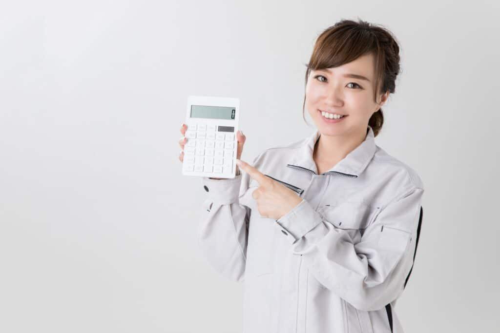 電卓を持つ作業着の女性