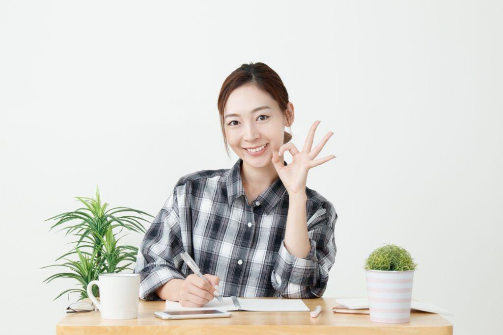 指で丸をつくる笑顔の女性