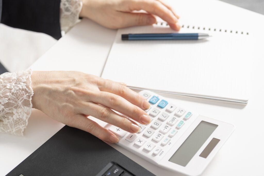 電卓で計算する女性の手、ノート