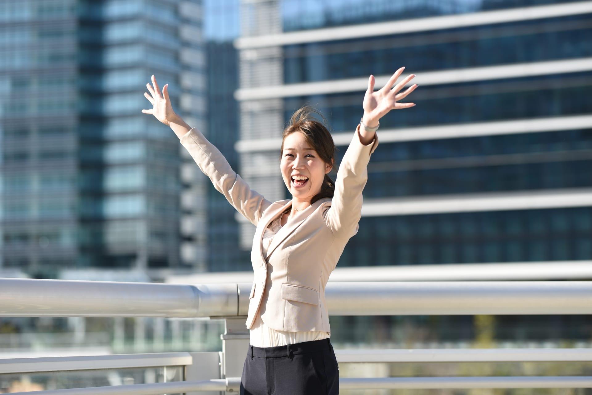オフィスの前で晴れ晴れする女性