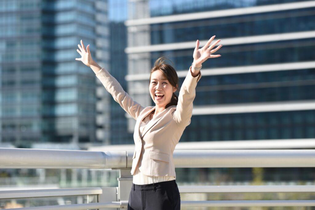 オフィス街で万歳する女性