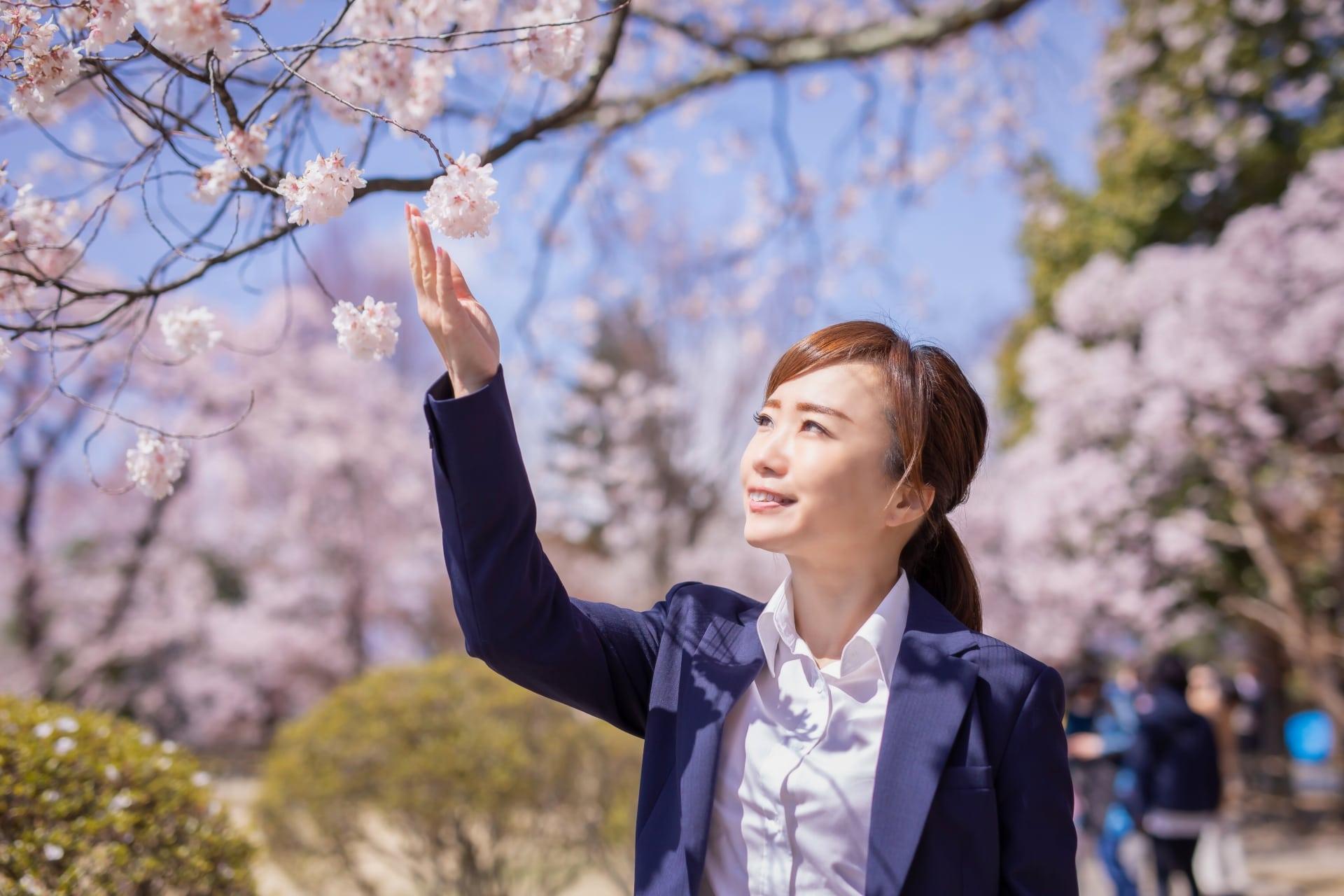 桜にふれる女性