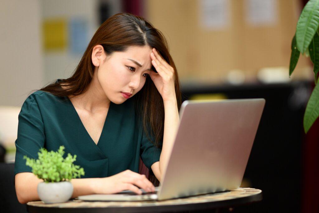 ノートパソコン、悩む女性