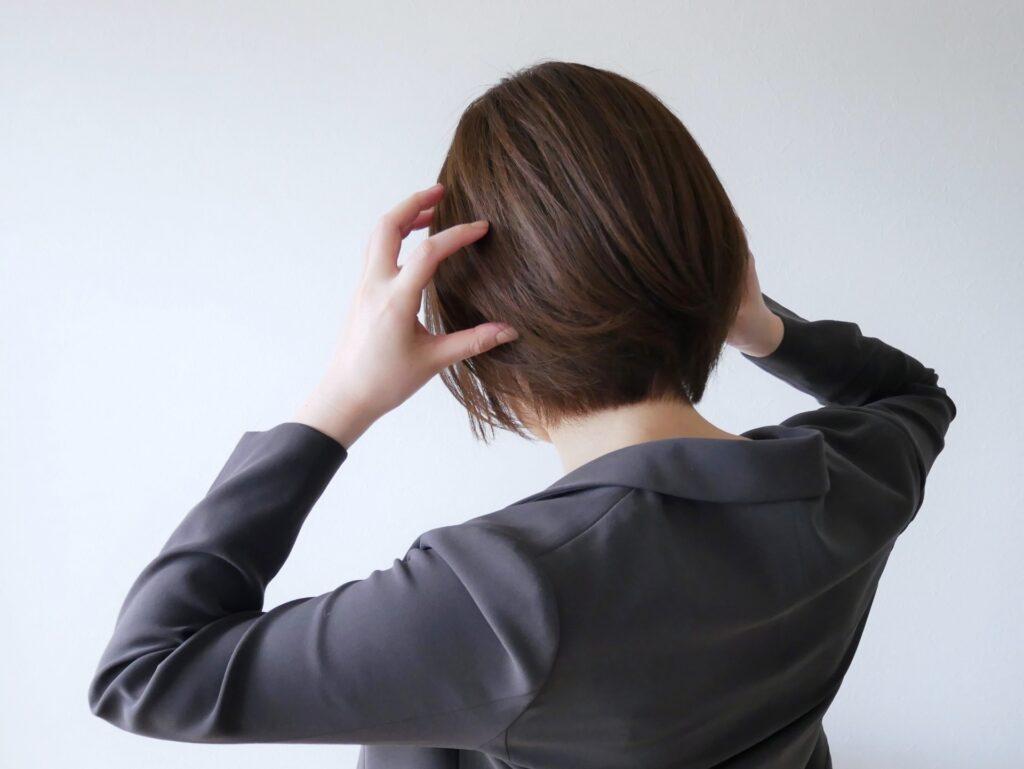 頭を抱えている女性、スーツ