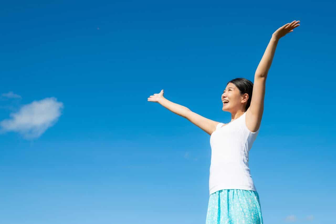 空に手をあげる女性