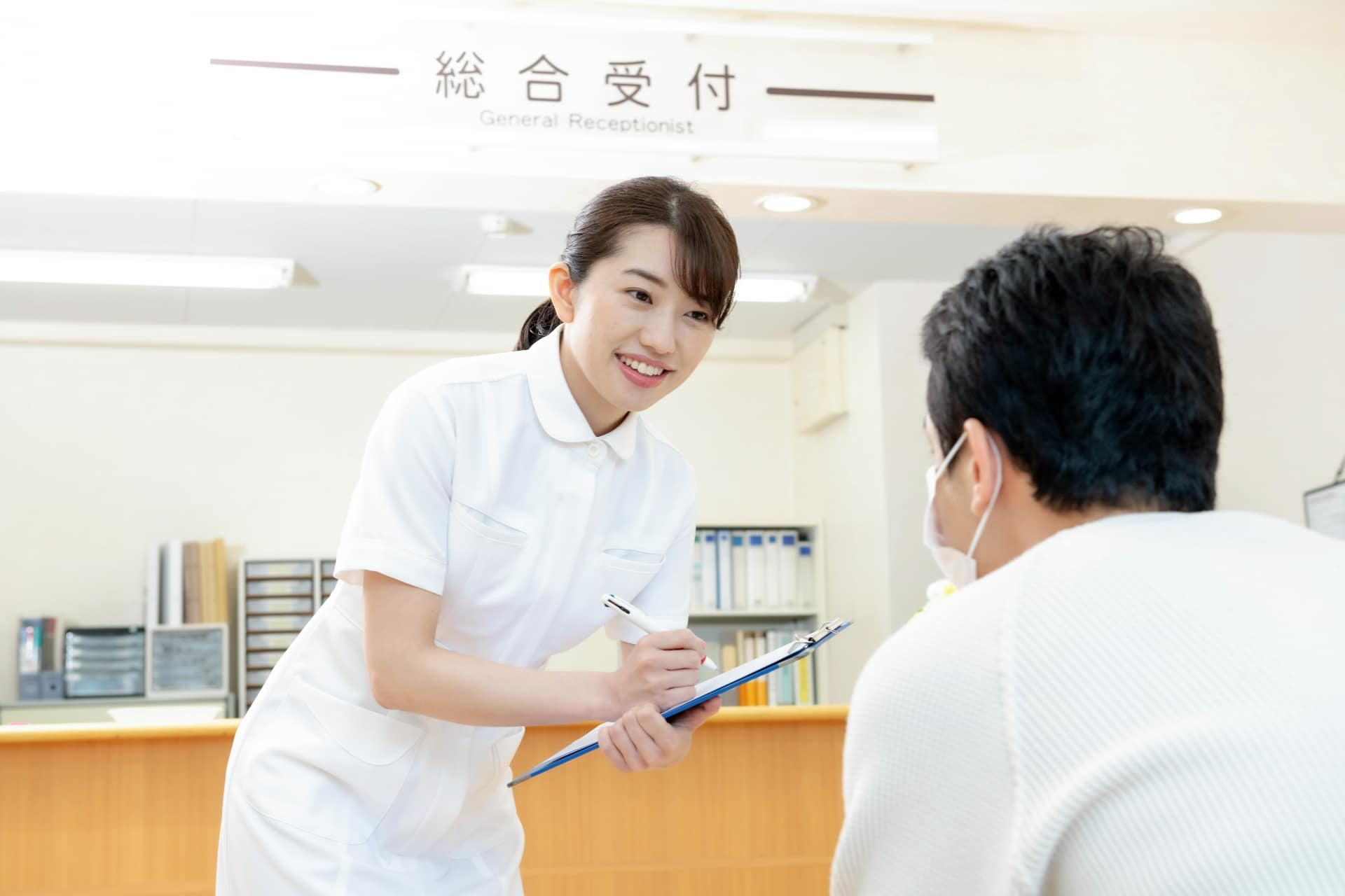 患者の様子を聞く医療事務の女性