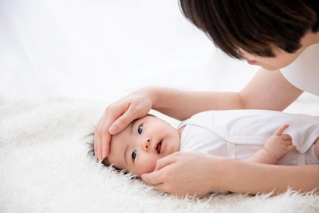 赤ちゃんの熱を測る女性