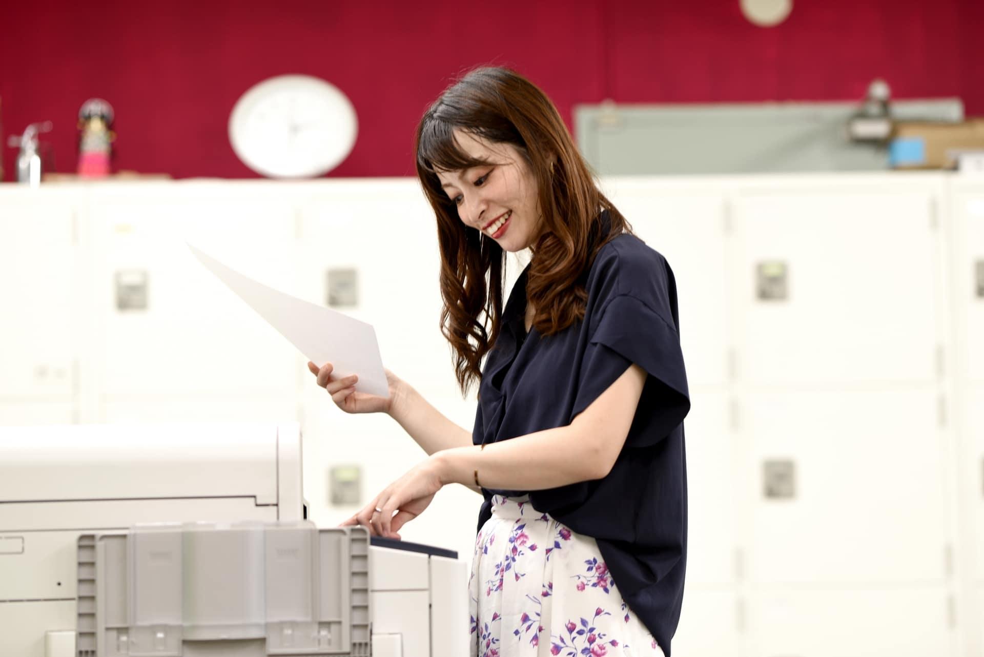 コピー機、プリンターを操作する女性