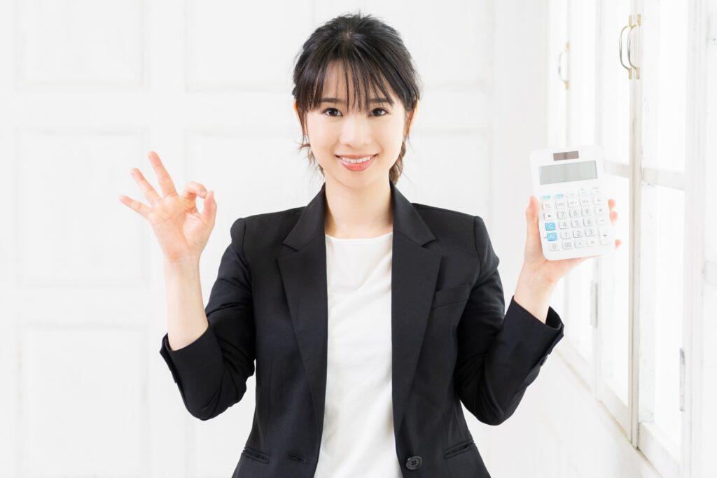 電卓を持つ笑顔の女性