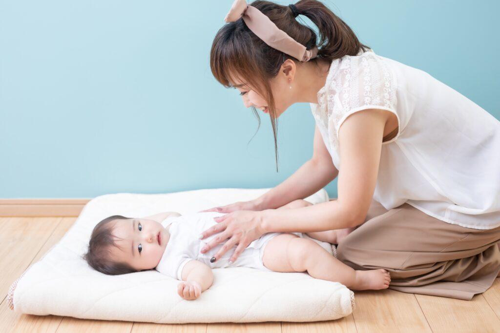 赤ん坊のおしめを変える女性