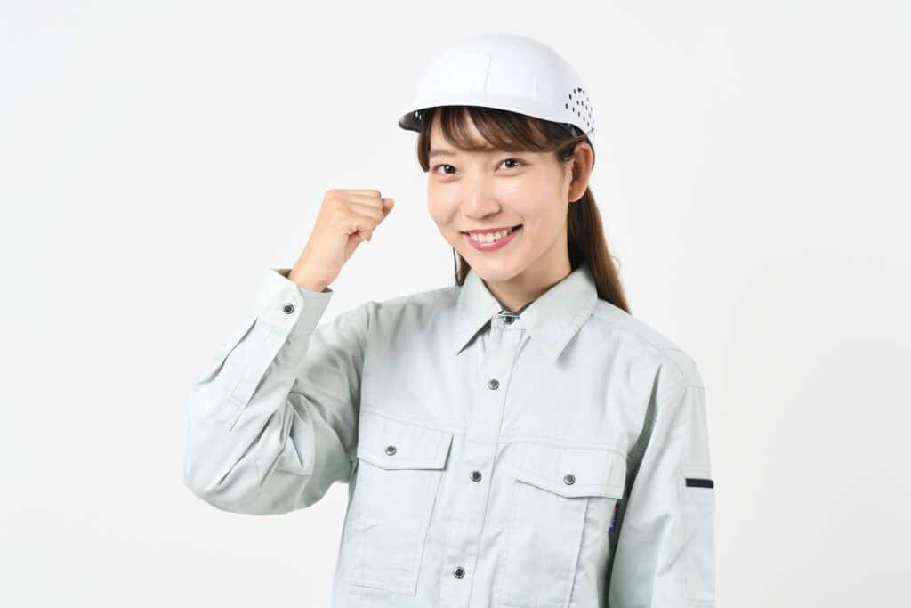 ガッツポーズをする作業着の女性