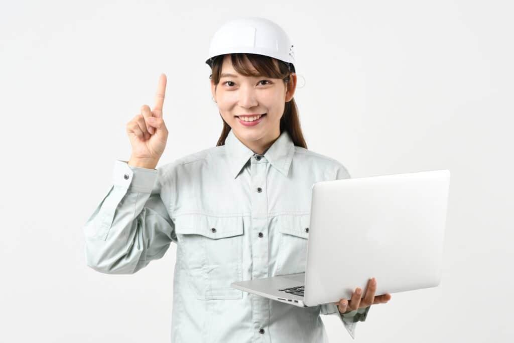 作業着の女性、ノートパソコン