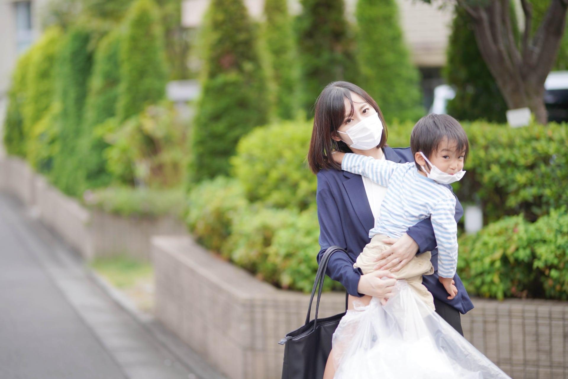 子供を抱っこしてゴミ捨てをする女性