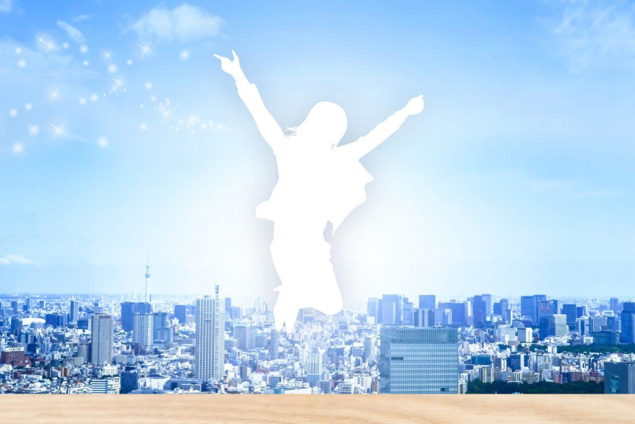 飛躍する女性シルエットと街並み