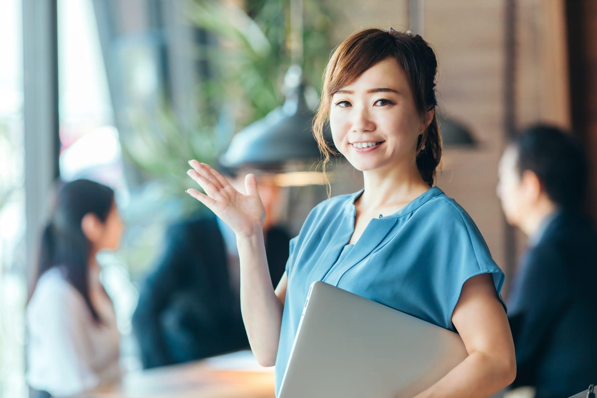 PCを持つ笑顔の女性