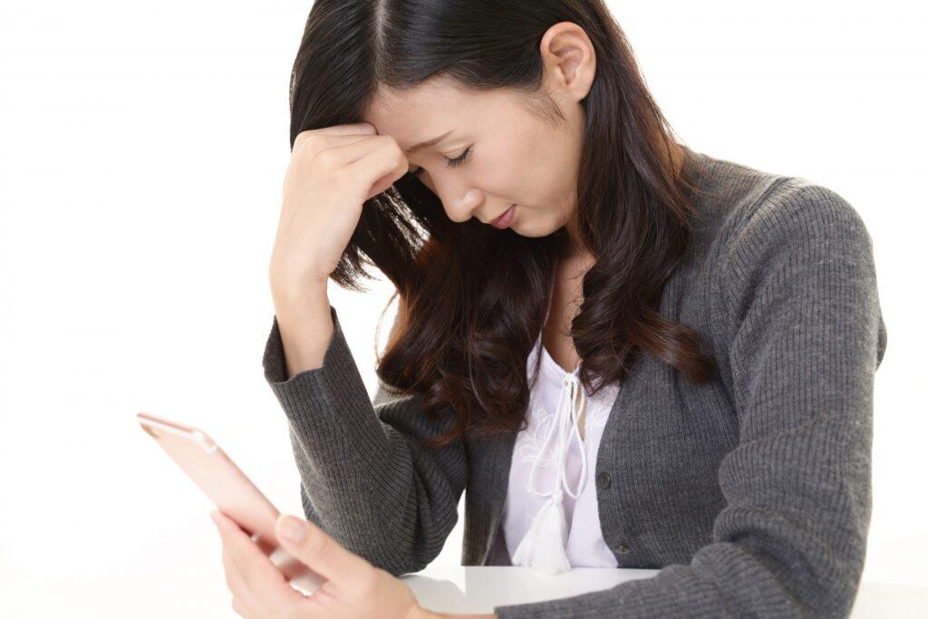 電話を手に悩む女性