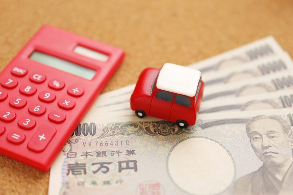 お金と電卓、車のフィギュア