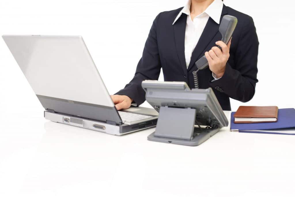 パソコンと電話を使う女性