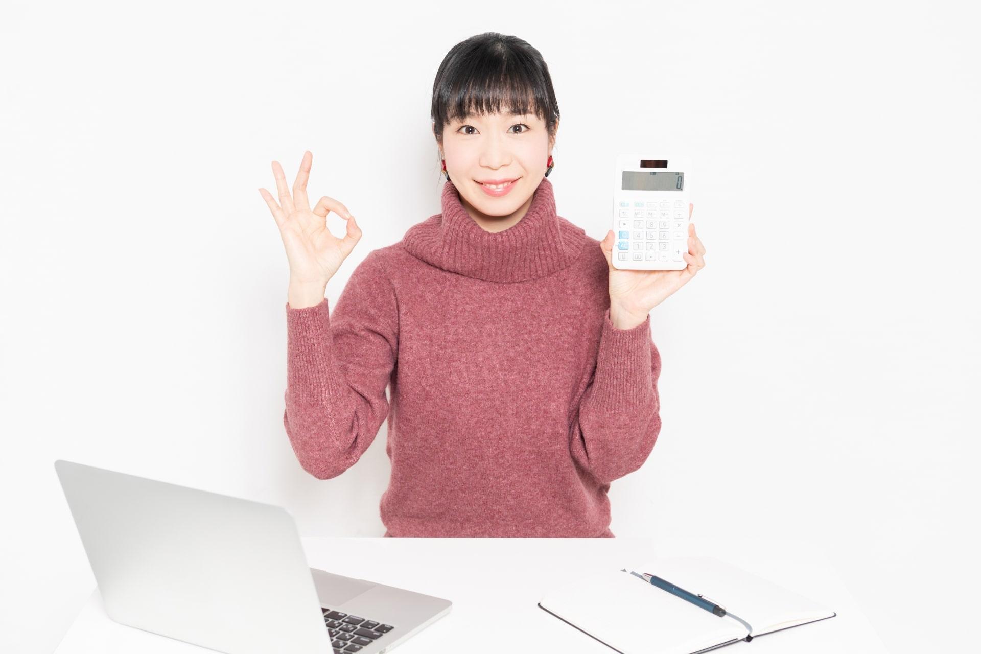 ノートパソコンと電卓を使う女性
