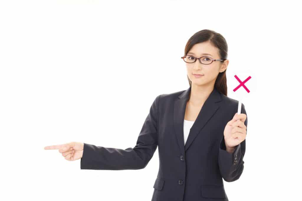 バツを持って指をさす女性