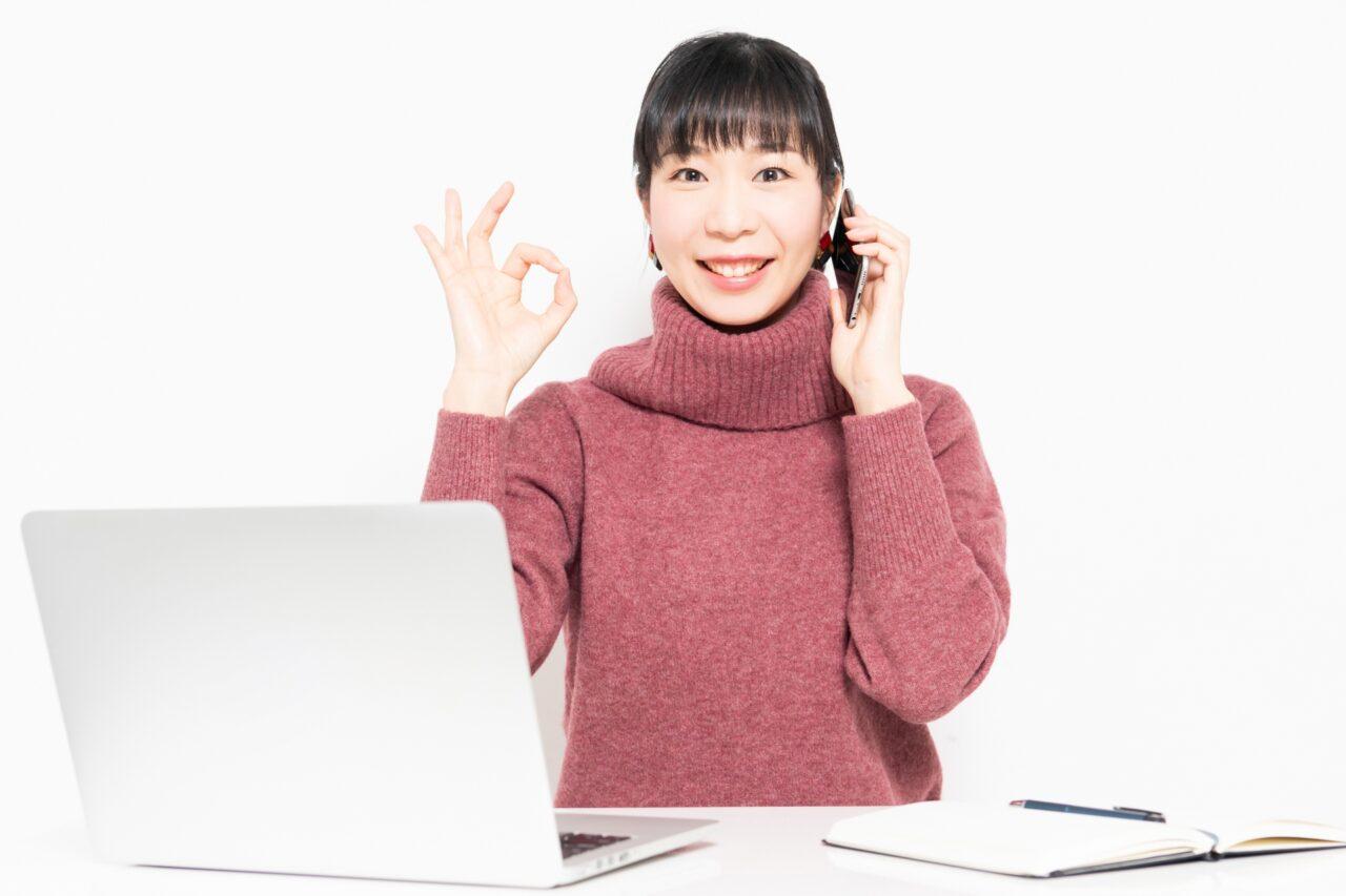 パソコンの前で電話を持つ女性