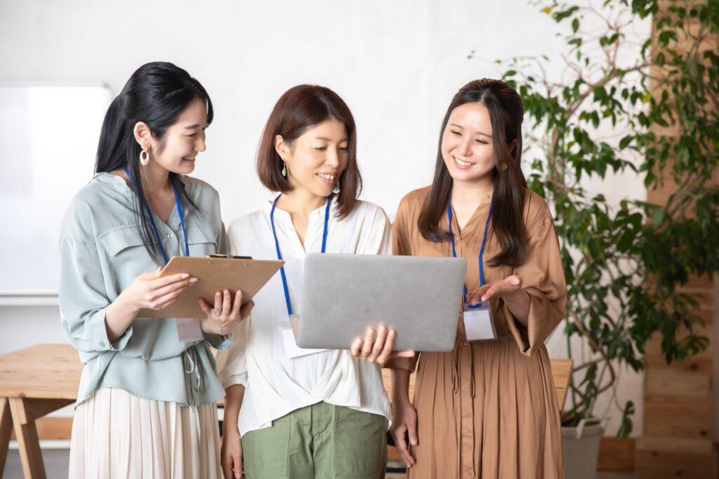 オフィス、ノートパソコン、会話する3人の女性