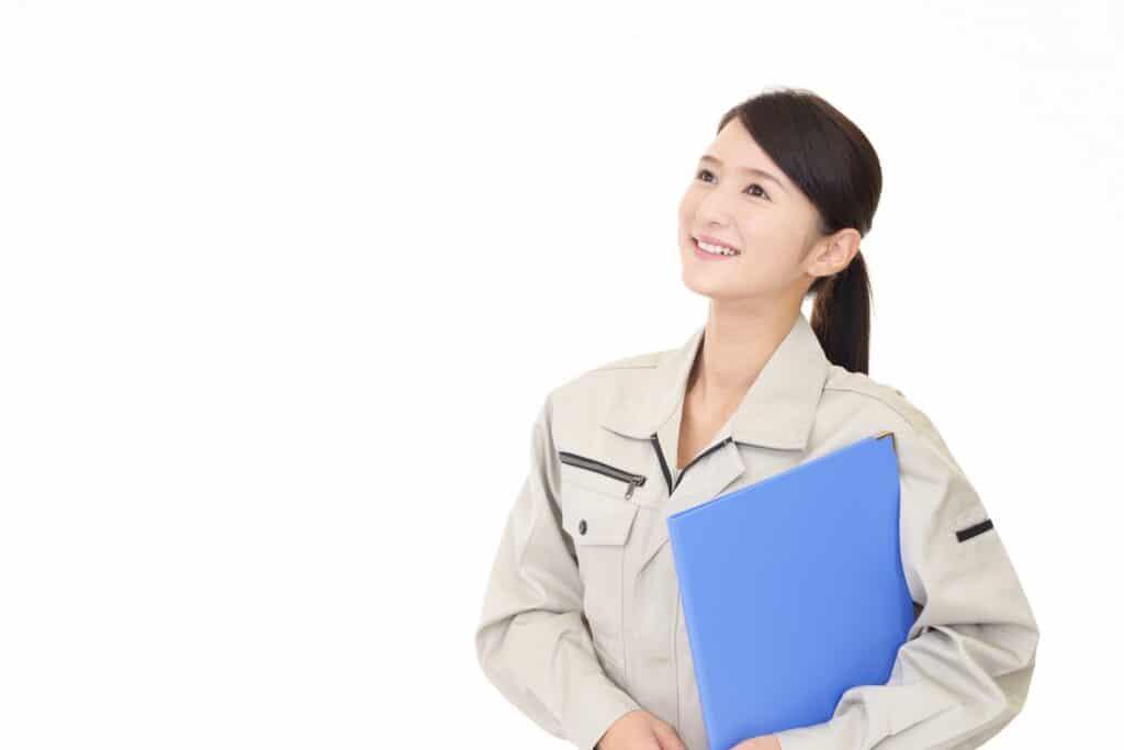 斜め上を見て書類を持つ作業着の女性