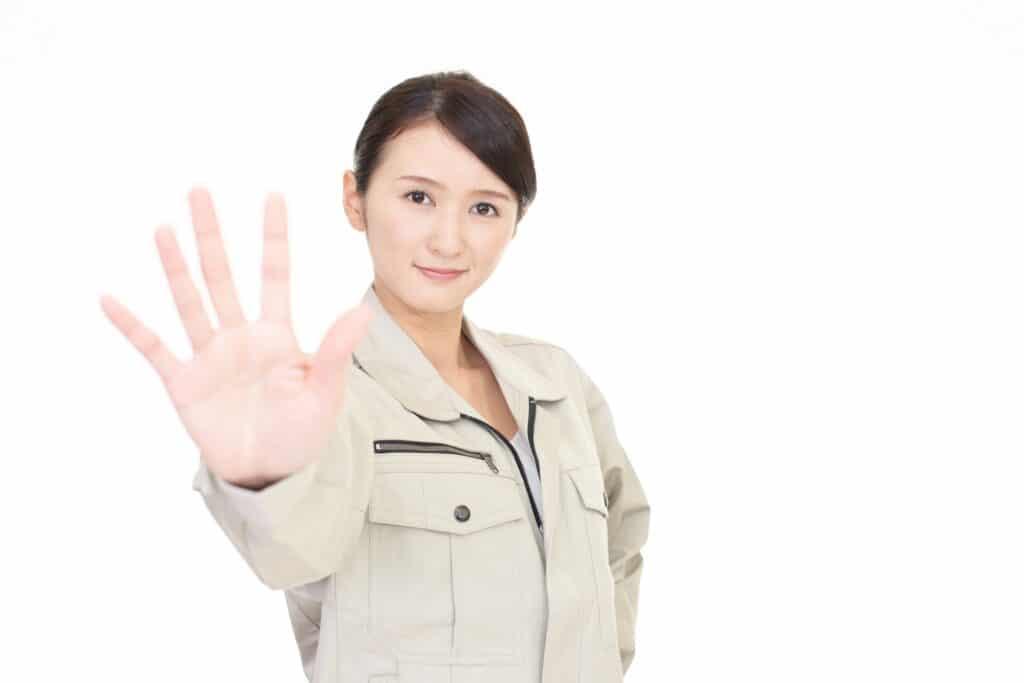 ストップのジェスチャーをする作業着の女性