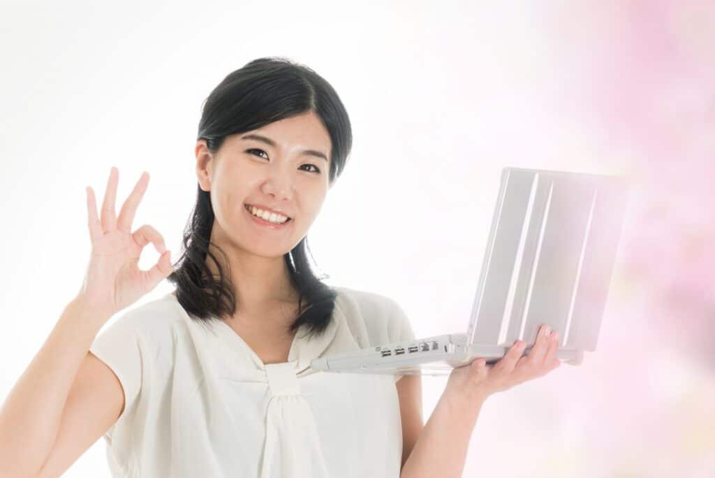 ノートパソコンを手にOKサインをする女性
